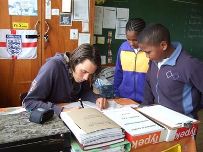 A volunteer grades his student's homework in South Africa, Africa.