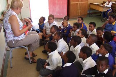 'A volunteer tells a story to her class in South Africa, Africa.