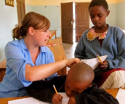 A volunteer helps one of her students with his homework in Tanzania, Africa.