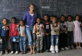 A volunteer stands at the blackboard with her class at our Teaching placement in Ethiopia.