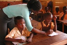 A Teaching volunteer works with a school student in Ghana, helping her to complete an English language exercise during class.