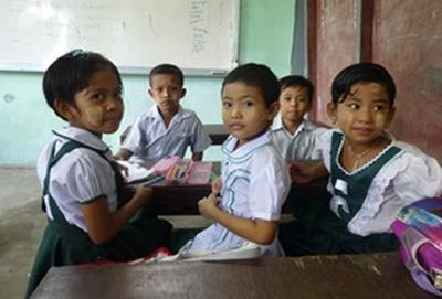 School children sit at their desk together during an English lesson at our volunteer Teaching placement in Myanmar.