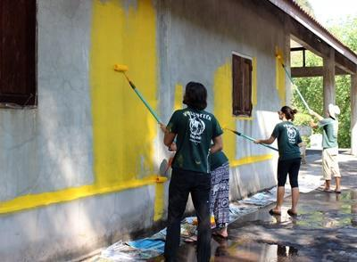 Projects Abroad short term Conservation volunteers painting a building overseas in Thailand, Asia