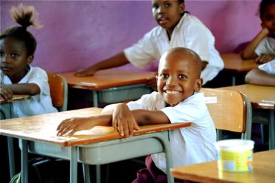 Small boy smiles at school in his classroom at a Projects Abroad Teaching placement in Tanzania