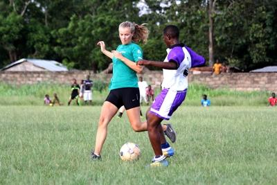 A female volunteer in Africa plays a football match at the Projects Abroad Togo Sports project
