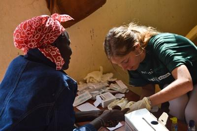 A female Projects Abroad medical volunteer in Africa treats an elderly Kenyan woman at a medical outreach centre near Nanuki, Kenya