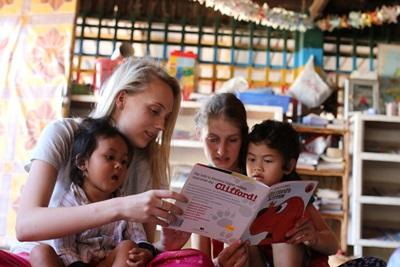 Young students who chose to volunteer abroad with Projects Abroad in Cambodia read with the children at a daycare centre