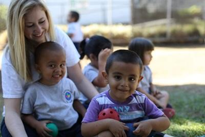 Projects Abroad volunteer, Maggie Everett, relaxes outside with the children from her care project in Costa Rica