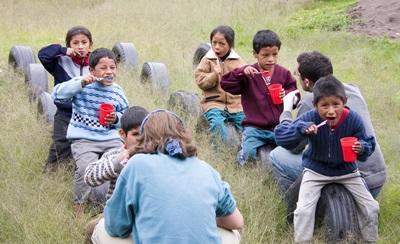 Volunteers educate children on brushing their teeth in Peru at care placement