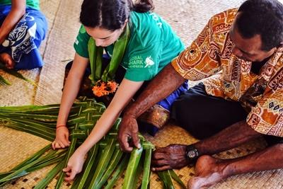 Projects Abroad Shark Conservation volunteer who travelled to Fiji gets a lesson in basket weaving from a local man in the village in Pacific Harbor