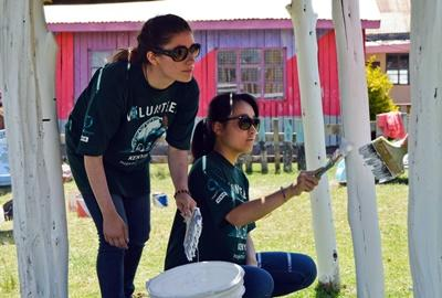 High School students volunteering abroad at a Care centre in Kenya, where they can be seen painting a jungle gym